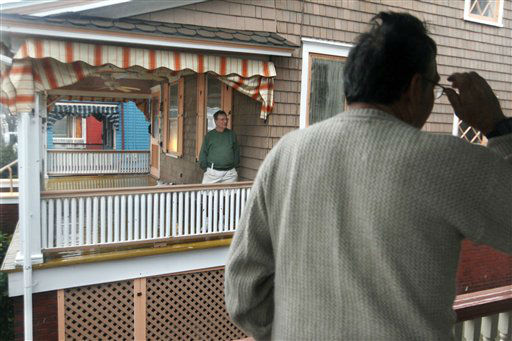 Neighbors, Don Schweikert, left, Mike Duvall, stand on the porches of their victorian homes Monday, Oct. 29, 2012, as Hurricane Sandy continues toward landfall. The neighbors say they would not evacuate because theirs is the highest street in Cape May, N.J., and has never flooded. The fast-strengthening Hurricane Sandy churned north Monday, raking ghost-town cities along the Northeast corridor with rain and wind gusts. The monster hurricane was expected to make a westward lurch and aim for New Jersey, blowing ashore Monday night and combining with two other weather systems - a wintry storm from the west and cold air rushing in from the Arctic - to create an epic superstorm.  <span class=meta>(AP Photo&#47; Mel Evans)</span>