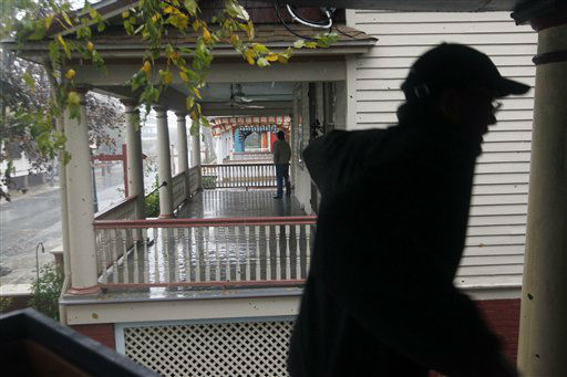 "<div class=""meta ""><span class=""caption-text "">While his neighbors talk on their porches, Cape May resident Dave Fitch checks on the lower level of his victorian home Monday, Oct. 29, 2012, in Cape May, N.J., as Hurricane Sandy continues toward landfall. The fast-strengthening Hurricane Sandy churned north Monday, raking ghost-town cities along the Northeast corridor with rain and wind gusts. The monster hurricane was expected to make a westward lurch and aim for New Jersey, blowing ashore Monday night and combining with two other weather systems - a wintry storm from the west and cold air rushing in from the Arctic - to create an epic superstorm.  (AP Photo/ Mel Evans)</span></div>"