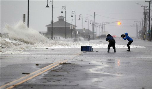 People photograph as rough surf of the Atlantic Ocean breaks over the beach and across Beach Ave., Monday morning, Oct. 29, 2012, in Cape May, N.J., as high tide and Hurricane Sandy begin to arrive. With Hurricane Sandy poised to make a direct hit on New Jersey, Gov. Chris Christie has issued a typically blunt warning to those thinking of riding it out in low-lying coastal areas: &#34;Don&#39;t be stupid. Get out.&#34; The storm was still hundreds of miles away, but was already making its approach known to New Jersey on Sunday with high winds, rough surf and coastal flooding as thousands of people fled to what they hoped would be safer ground.  <span class=meta>(AP Photo&#47; Mel Evans)</span>