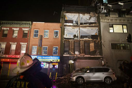 Firefighters look up at the facade of a four-story building on 14th Street and 8th Avenue that collapsed onto the sidewalk Monday, Oct. 29, 2012, in New York. Hurricane Sandy bore down on the Eastern Seaboard&#39;s largest cities Monday, forcing the shutdown of mass transit, schools and financial markets, sending coastal residents fleeing, and threatening a dangerous mix of high winds, soaking rain and a surging wall of water up to 11 feet tall.  <span class=meta>(AP Photo&#47; John Minchillo)</span>