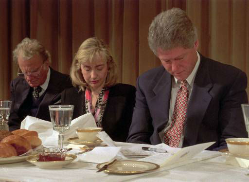 President and Mrs. Clinton, along with Rev. Billy Graham bow their heads during the annual National Prayer Breakfast in Washington Feb.4, 1993. The president joined leaders of Washington&#39;s political and military establishment at the annual prayer event.  <span class=meta>(AP Photo&#47;Greg Gibson)</span>