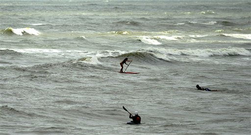 A lone paddle boarder, surfer and kayaker head into the waves breaking several hundred yards off the beach of Tybee Island, Ga., as Hurricane Irene makes its way up the east coast, Thursday, Aug. 25, 2011. Tybee, one of Georgia&#39;s few island communities, is only expecting high surf from Hurricane Irene as the storm passes to the west on Friday.  <span class=meta>(AP Photo&#47; Stephen Morton)</span>