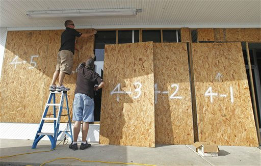"<div class=""meta image-caption""><div class=""origin-logo origin-image ""><span></span></div><span class=""caption-text"">Richard Baker, left, and Jonathan Willis, right, cover the windows to the family business in Morehead City, N.C., Thursday, Aug. 25, 2011 as Hurricane Irene heads toward the North Carolina coast.  A monstrous Hurricane Irene tightened its aim on the Eastern Seaboard, Thursday, threatening 65 million people along a shore-hugging path from North Carolina to New England.  (AP Photo/ Chuck Burton)</span></div>"