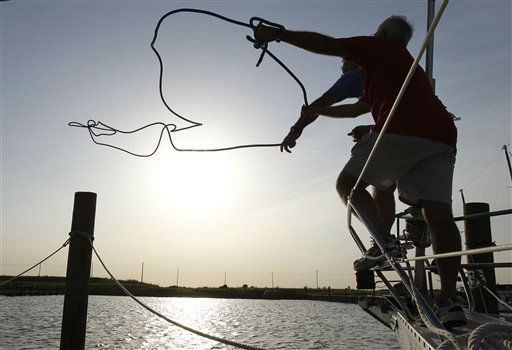 Gary Stull, of Norfolk, front, and Kord Christianson, of Willoughby Spit, throw a line to secure a boat in preparation for the arrival of Hurricane Irene in the Willoughby Spit area of  Norfolk, Va., Thursday, Aug. 25, 2011.  <span class=meta>(AP Photo&#47; Steve Helber)</span>