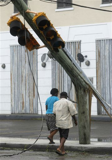 A couple walks past a downed light pole in the aftermath of Hurricane Irene in Nassau, on New Providence Island in the Bahamas, Thursday, Aug. 25, 2011. Irene hit Nassau with tropical storm strength winds as it passed to the east.  <span class=meta>(AP Photo&#47; Lynne Sladky)</span>