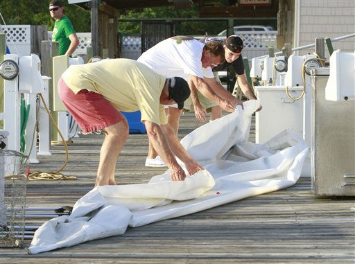 Joe Phibbs, left, of Chesapeake, Va. Zell Walker, of Hampton, Va., center, and Eric Welp of Md., fold a sail in preparation for the arrival of Hurricane Irene in the Willoughby Spit area of  Norfolk, Va., Thursday, Aug. 25, 2011.  <span class=meta>(AP Photo&#47; Steve Helber)</span>