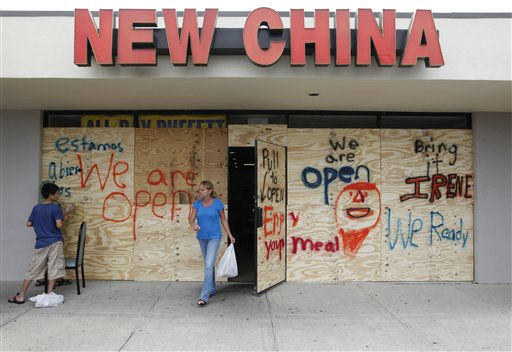 Resident Jeanette Walton, who said she is staying and not heeding the mandatory evacuation order, carries her Chinese take out food from a boarded up restaurant in preparation for the arrival of Hurricane Irene in Nags Head, N.C., Friday, Aug. 26, 2011 on North Carolina&#39;s Outer Banks.  <span class=meta>(AP Photo&#47; Charles Dharapak)</span>