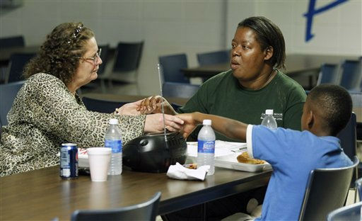 Sheila Moore, center, prays with her son Anthony, right, and friend Debra Jones, left, before eating a meal at an emergency shelter in Morehead City, N.C., Friday, Aug. 26, 2011 as Hurricane Irene heads toward the North Carolina coast.  <span class=meta>(AP Photo&#47; Chuck Burton)</span>