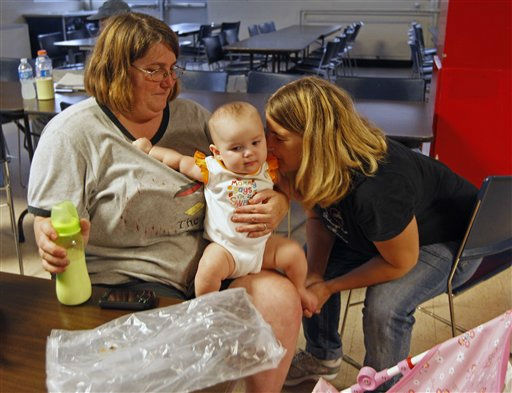 Susan Kinchen, left, and her daughter Brittany Burns, right, play with Brittany&#39;s daughter Anna Burns, 5 month., center, at an emergency shelter in Morehead City, N.C., Friday, Aug. 26, 2011 as Hurricane Irene heads toward the North Carolina coast.  <span class=meta>(AP Photo&#47; Chuck Burton)</span>