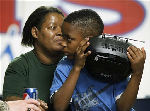 Anthony Moore, 10, front, from listens to weather reports on a radio as he sits with his mother Sheila Moore, back, at an emergency shelter in Morehead City, N.C., Friday, Aug. 26, 2011 as Hurricane Irene heads toward the North Carolina coast. <span class=meta>(AP Photo&#47; Chuck Burton)</span>
