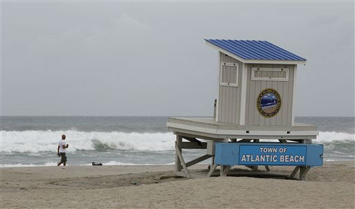 A man walks his dog past a closed lifeguard station in Atlantic Beach, N.C., Friday, Aug. 26, 2011, as Hurricane Irene heads toward the North Carolina coast.  <span class=meta>(AP Photo&#47; Chuck Burton)</span>