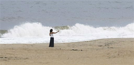 With heightened waves hitting the beach a woman takes photographs in Nags Head, N.C., Friday, Aug. 26, 2011, on North Carolina&#39;s Outer Banks. <span class=meta>(AP Photo&#47; Charles Dharapak)</span>