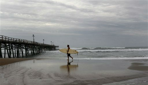 "<div class=""meta ""><span class=""caption-text "">A surfer runs along the beach in Atlantic Beach, N.C., Friday, Aug. 26, 2011 as Hurricane Irene heads toward the North Carolina coast.  (AP Photo/ Chuck Burton)</span></div>"