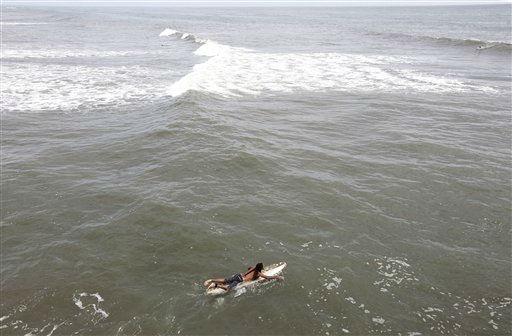 A surfer paddles out hoping to catch some big waves ahead of the arrival of Hurricane Irene in Nags Head, N.C., Friday, Aug. 26, 2011 on North Carolina&#39;s Outer Banks.  <span class=meta>(AP Photo&#47; Charles Dharapak)</span>