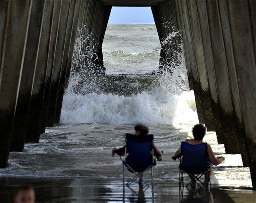 Visitors from Dahlonega, Ga., watch the surf crash into the pylons under the pier on Tybee Island, Ga., Wednesday, Aug. 24, 2011, as Hurricane Irene heads towards South Florida. Forecasters are predicting that Irene will strike North Carolina&#39;s Outer Banks on Saturday.  <span class=meta>(AP Photo)</span>