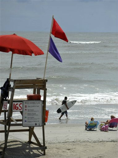 A surfer walks along the water line near a lifeguard station flying a beach hazard flag to warn of dangerous rip currents Wednesday, Aug. 24, 2011, on Tybee Island, Ga. Forecasters are predicting that Hurricane Irene will strike North Carolina&#39;s Outer Banks on Saturday.  <span class=meta>(AP Photo)</span>