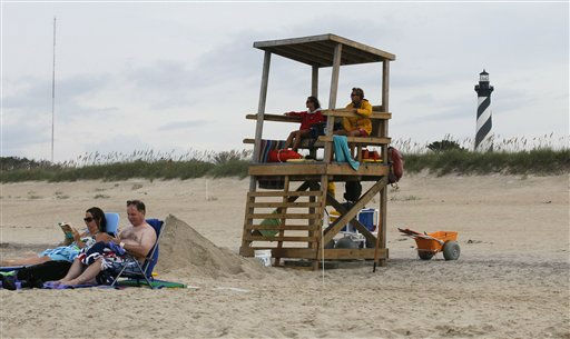 "<div class=""meta image-caption""><div class=""origin-logo origin-image ""><span></span></div><span class=""caption-text"">People sit in the sand at Cape Hatteras National Seashore in Buxton, N.C., Wednesday, Aug. 24, 2011. As Hurricane Irene strengthened to a major Category 3 storm over the Bahamas Wednesday, it continues to threaten much of the east coast as it is expected to get stronger over warm ocean waters and could become a Category 4 storm with winds of at least 131 mph (211 kph) by Thursday.  (AP Photo)</span></div>"