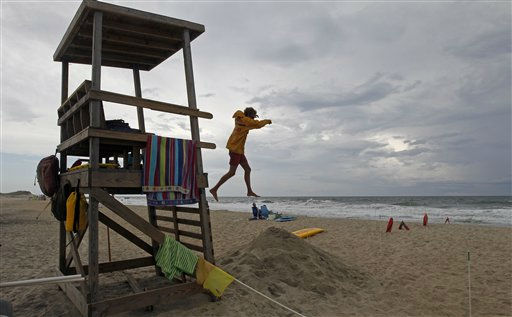 Lifeguard Kyle Walsh jumps from his stand to warn swimmers of lightning along the Cape Hatteras National Seashore in Buxton, N.C., Wednesday, Aug. 24, 2011. As Hurricane Irene strengthened to a major Category 3 storm over the Bahamas Wednesday, it continues to threaten much of the east coast as it is expected to get stronger over warm ocean waters and could become a Category 4 storm with winds of at least 131 mph &#40;211 kph&#41; by Thursday. <span class=meta>(AP Photo)</span>