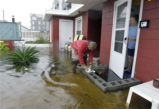 Tim Dickens, left, piles sandbags in front of the door as landlady Mary Jane Lane, right, watches in Carolina Beach, N.C., Thursday, Sept. 30, 2010.  <span class=meta>(AP Photo&#47; Chuck Burton)</span>
