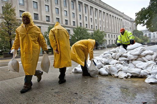 As rain from Hurricane Sandy arrives in Washington, workers haul sandbags to shore up vulnerable spots at The Pavilion at the Old Post Office, Monday, Oct. 29, 2012, in Washington. The Justice Department is seen in the background.   <span class=meta>(AP Photo&#47; J. Scott Applewhite)</span>