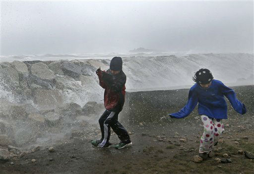 Youngsters run as waves crash against a seawall in Scituate, Mass. Monday, Oct. 29, 2012.  <span class=meta>(AP Photo&#47; Elise Amendola)</span>