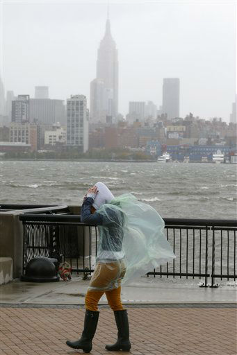 Heather Maschi, 24, tries to keep her hood on as gusty winds blow near the Hudson River, Monday, Oct. 29, 2012, in Hoboken, N.J.  <span class=meta>(AP Photo&#47; Julio Cortez)</span>