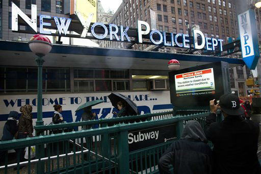 Pedestrians pass a New York Police Department station beside a closed subway entrance at Times Square, Monday, Oct. 29, 2012, in New York.  <span class=meta>(AP Photo&#47; John Minchillo)</span>