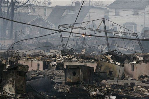 "<div class=""meta ""><span class=""caption-text "">Homes damaged by a fire at Breezy Point, in the New York City borough of Queens smolder Tuesday, Oct. 30, 2012.  (AP Photo/ Frank Franklin II)</span></div>"