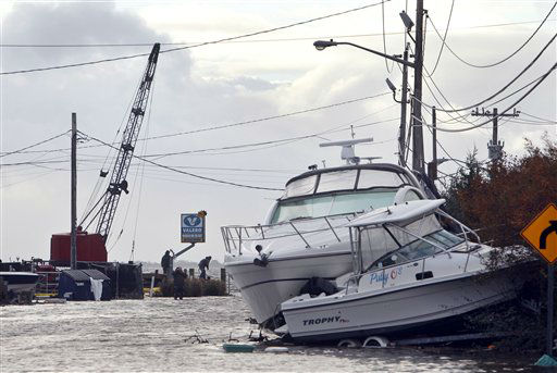 "<div class=""meta ""><span class=""caption-text "">Boats lie piled up as people work to secure a fuel dock in the wake of superstorm Sandy, Tuesday, Oct. 30, 2012, in West Babylon, N.Y. (AP Photo/ Jason DeCrow)</span></div>"
