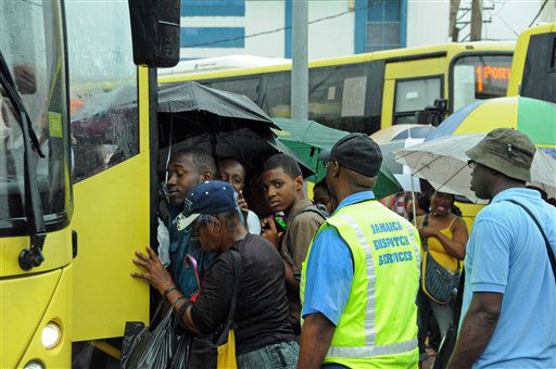 Commuters board a bus as rain brought by the outer bands of Tropical Storm Sandy fall in Kingston, Jamaica, Tuesday, Oct. 23, 2012.