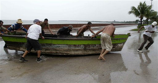 People remove a boat from the water ahead of the arrival of Hurricane Sandy in Manzanillo, Cuba, Wednesday, Oct. 24, 2012.