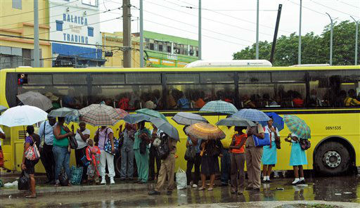 Commuters wait at a bus stop as rain brought by the outer bands of Tropical Storm Sandy falls in Kingston, Jamaica, Tuesday, Oct. 23, 2012.