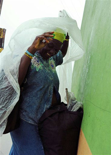 Pauline Daley covers herself as rain brought by the outer bands of Tropical Storm Sandy falls in Kingston, Jamaica, Tuesday, Oct. 23, 2012.