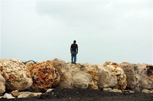 A man stands on boulders placed as a barrier to...