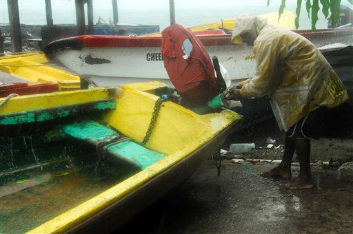 Fisherman Hubert Dowie works to secure his boat before the arrival of Hurricane Sandy in Port Royal, Jamaica, Wednesday, Oct. 24, 2012.