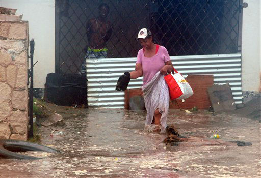 A woman wades through flood water brought by...