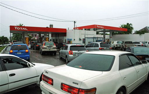 Drivers wait to fill their cars with fuel as rain brought by the outer bands of Tropical Storm Sandy fall in Kingston, Jamaica, Tuesday, Oct. 23, 2012.