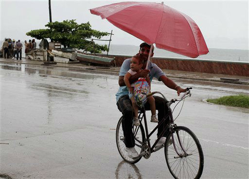 A man balances a child and umbrella on his bike as it rains during the approach of Hurricane Sandy in Manzanillo, Cuba, Wednesday, Oct. 24, 2012.
