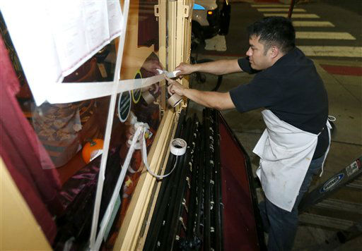 "<div class=""meta ""><span class=""caption-text "">Oswaldo Falleres puts tape on the window of a restaurant in preparation for the arrival of superstorm Sandy, Sunday, Oct. 28, 2012, in Hoboken, N.J.  (AP Photo/ Julio Cortez)</span></div>"