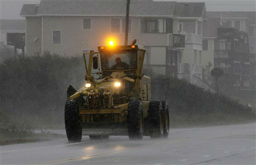 Earth moving equipment drives south along Virginia Dare Trail in the rain and wind generated by Hurricane Sandy in Kill Devil Hills, N.C., Sunday, Oct. 28, 2012. <span class=meta>(AP Photo&#47; Gerry Broome)</span>