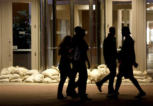 Sandbags line the entrance of a building as people walk by near the Hudson River water front, Sunday, Oct. 28, 2012, in Hoboken, N.J.  <span class=meta>(AP Photo&#47; Julio Cortez)</span>
