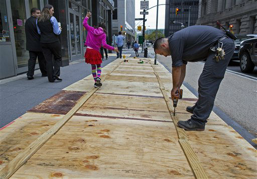 A maintenance worker named Vitto attaches plywood to a sidewalk grate at the 2 Broadway building of Lower Manhattan in New York, Sunday, Oct. 28, 2012, as a child walking by takes advantage of the temporary structure.  <span class=meta>(AP Photo&#47; Craig Ruttle)</span>