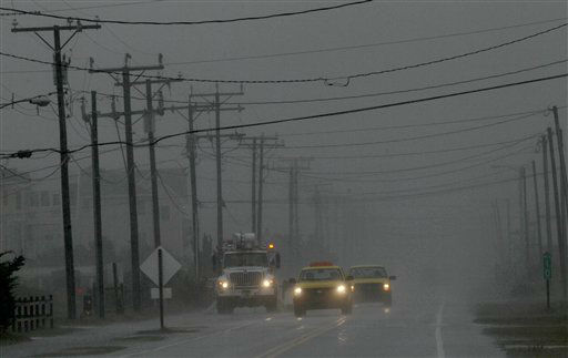 Utilities and state road workers monitor the situation on Virginia Dare Trail as rain and wind from Hurricane Sandy engulf the beachfront road in Kill Devil Hills, N.C., Sunday, Oct. 28, 2012.  <span class=meta>(AP Photo&#47; Gerry Broome)</span>
