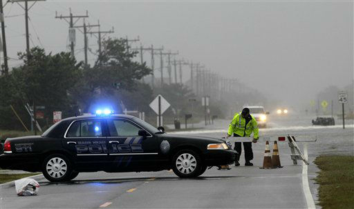 "<div class=""meta ""><span class=""caption-text "">A police officer sets up a road block on South Oregon Inlet Road as water from Hurricane Sandy covers the road in Nags Head, N.C., Sunday, Oct. 28, 2012.  (AP Photo/ Gerry Broome)</span></div>"