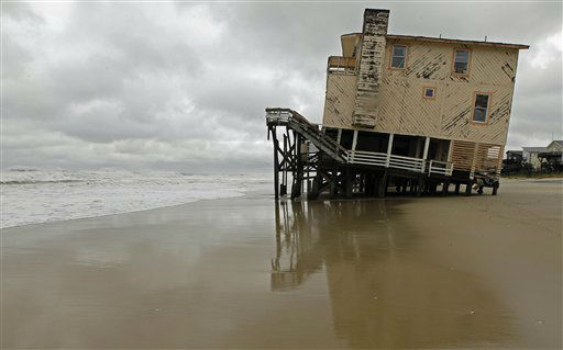 "<div class=""meta ""><span class=""caption-text "">An abandoned beach house that survived the storm surge from Hurricane Sandy sits off center in Nags Head, N.C., Monday, Oct. 29, 2012.  (AP Photo/ Gerry Broome)</span></div>"