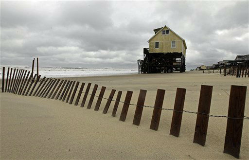 "<div class=""meta ""><span class=""caption-text "">Sand blown in by the wind and storm surge from Hurricane Sandy piles up along a dune fence in front of an abandoned beach house in Nags Head, N.C., Monday, Oct. 29, 2012.  (AP Photo/ Gerry Broome)</span></div>"