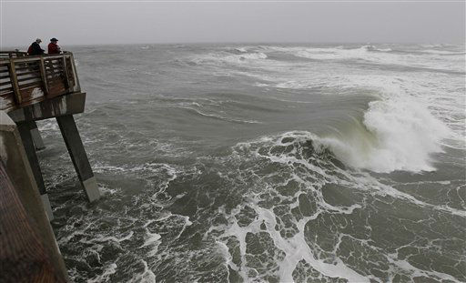 "<div class=""meta ""><span class=""caption-text "">Huge waves crash as onlookers peer from Jeanette's Pier in Nags Head, N.C.,  as Hurricane Sandy churns up the east coast  Saturday, Oct. 27, 2012.  (AP Photo/ Gerry Broome)</span></div>"