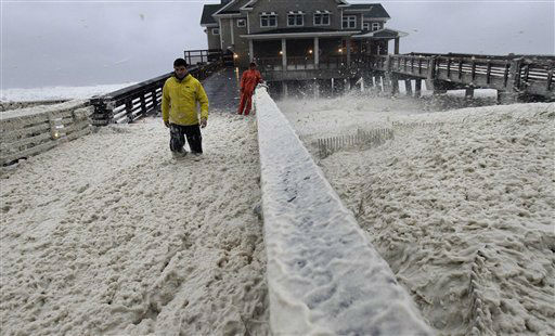 A news crew wades through sea foam blown onto Jeanette&#39;s Pier in Nags Head, N.C., Sunday, Oct. 28, 2012. <span class=meta>(AP Photo&#47; Gerry Broome)</span>