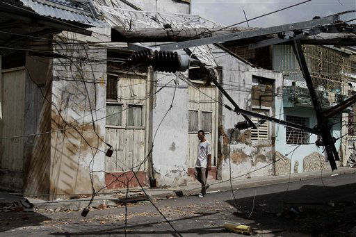 "<div class=""meta ""><span class=""caption-text "">A man walks along a street where electrical lines hang damaged by Hurricane Sandy in Santiago de Cuba, Cuba, Friday Oct. 26, 2012. (AP Photo/ Franklin Reyes)</span></div>"