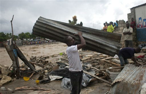 "<div class=""meta ""><span class=""caption-text "">A resident carries a metal sheet, part of a damaged house after heavy rains brought by Hurricane Sandy in Port-au-Prince, Haiti, Thursday, Oct. 25,  2012.  (AP Photo/ Dieu Nalio Chery)</span></div>"